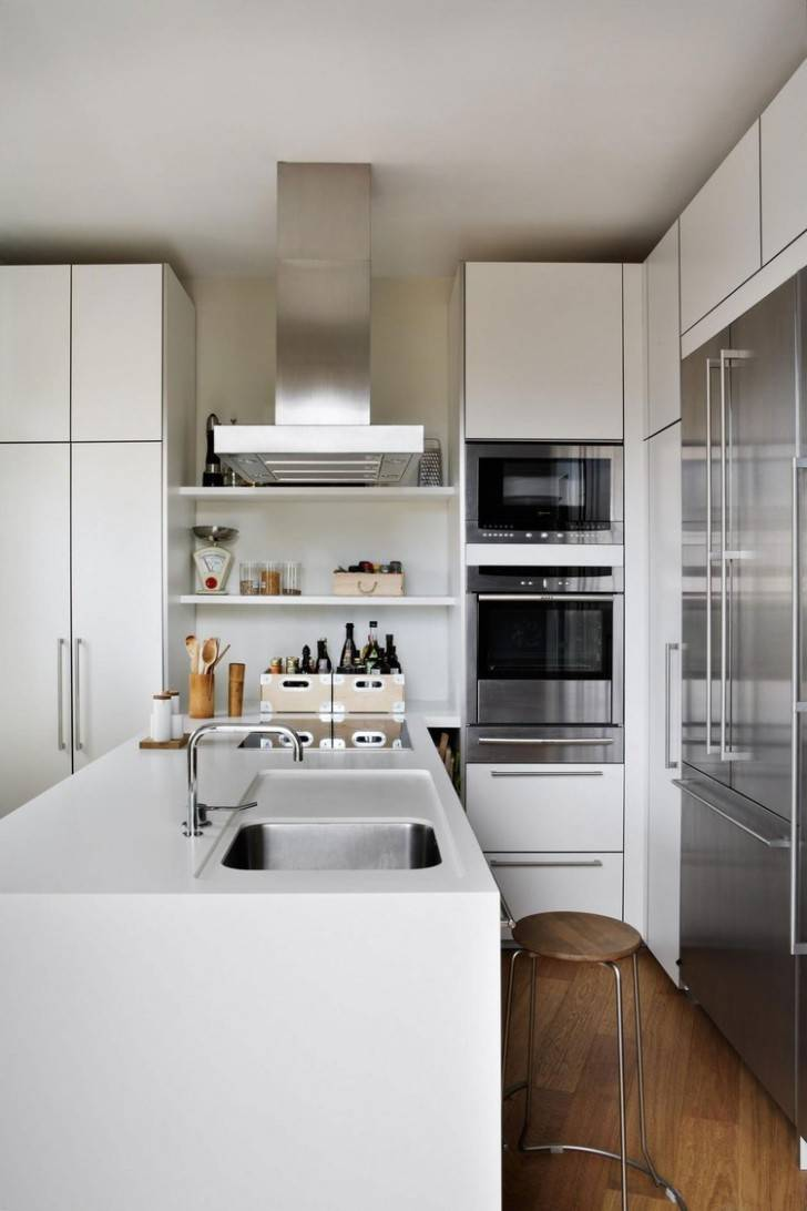20 - Alluring contemporary penthouse kitchen rectangle shape white kitchen island composite kitchen sink white kitchen cabinets built in oven built in fridge built in stoves stainless steel cooker hood