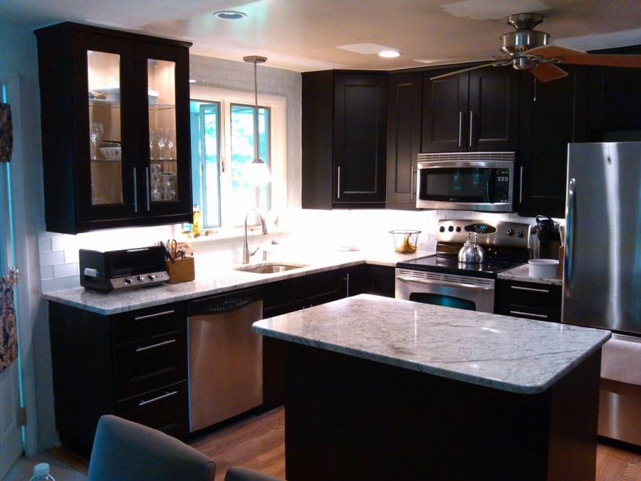 Contemporary kitchen with dark wood cabinets and white marble counters