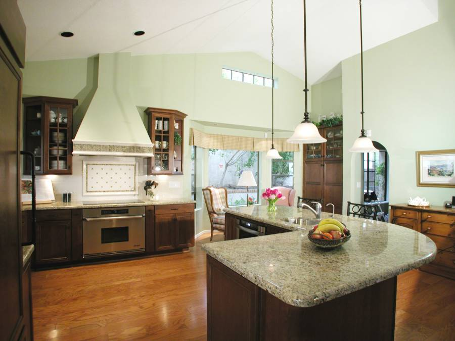 Contemporary kitchen with light granite counters dark wood island