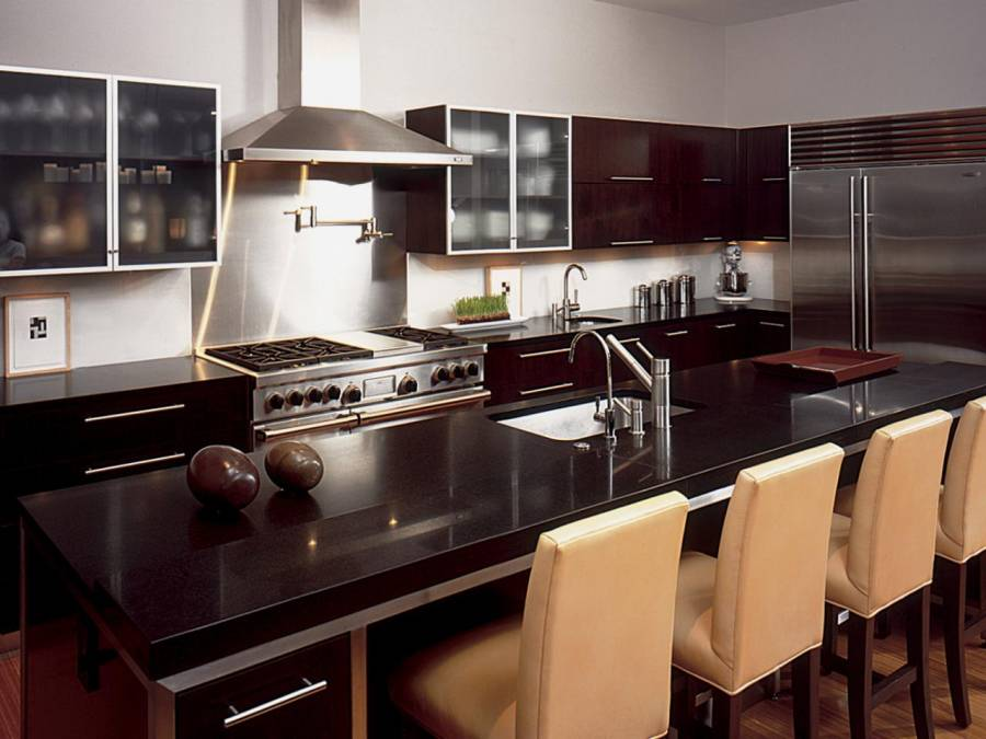 Kitchen with open layout, limestone flooring and dark cabinetry