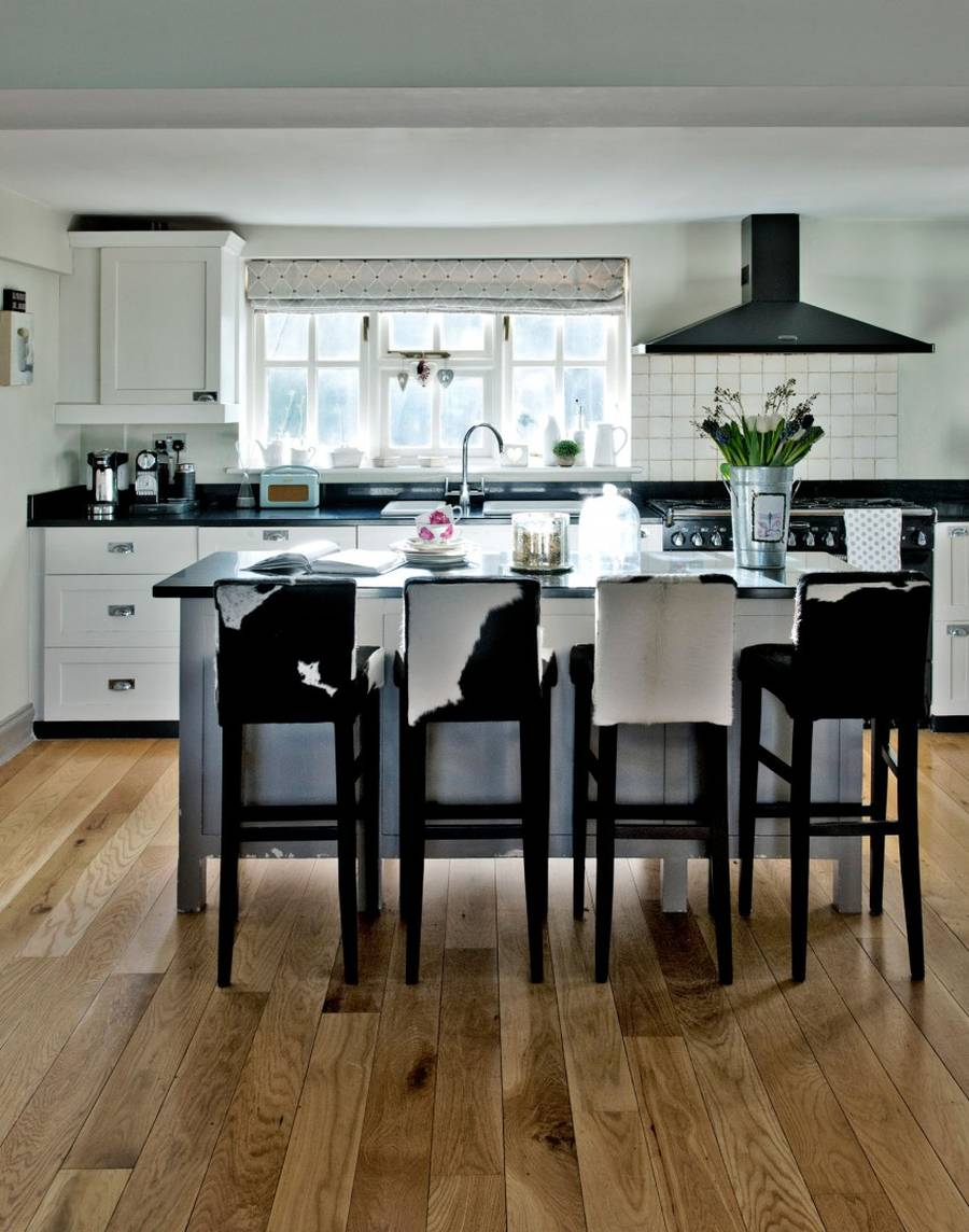 White Country Kitchen with Black Worktop and Cowhide Bar Stools