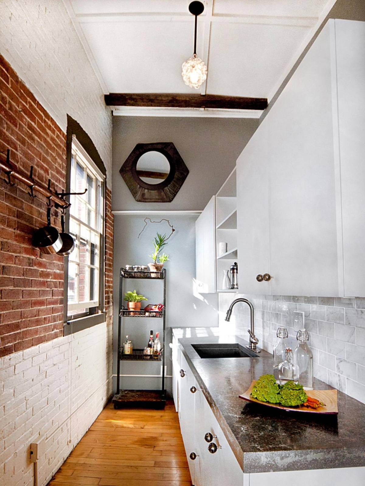 Great design of modern and small loft kitchen with bricks wall and galley style layout