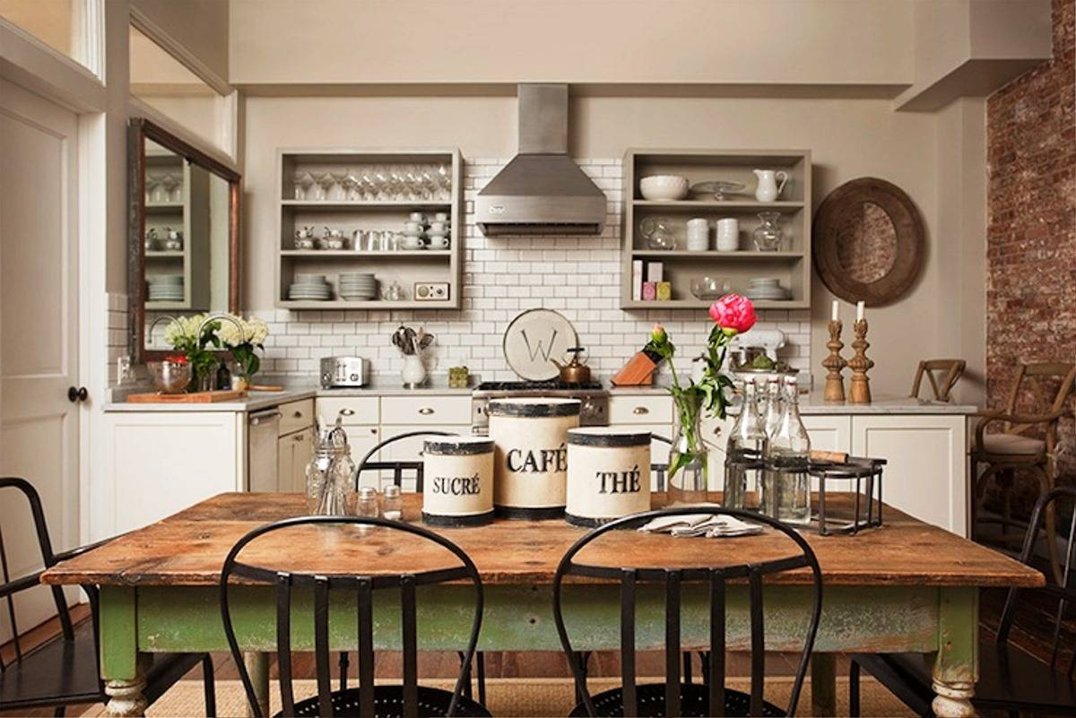 Idea for industrial farmhouse kitchen decor with brick walls and metall stools at the dining area