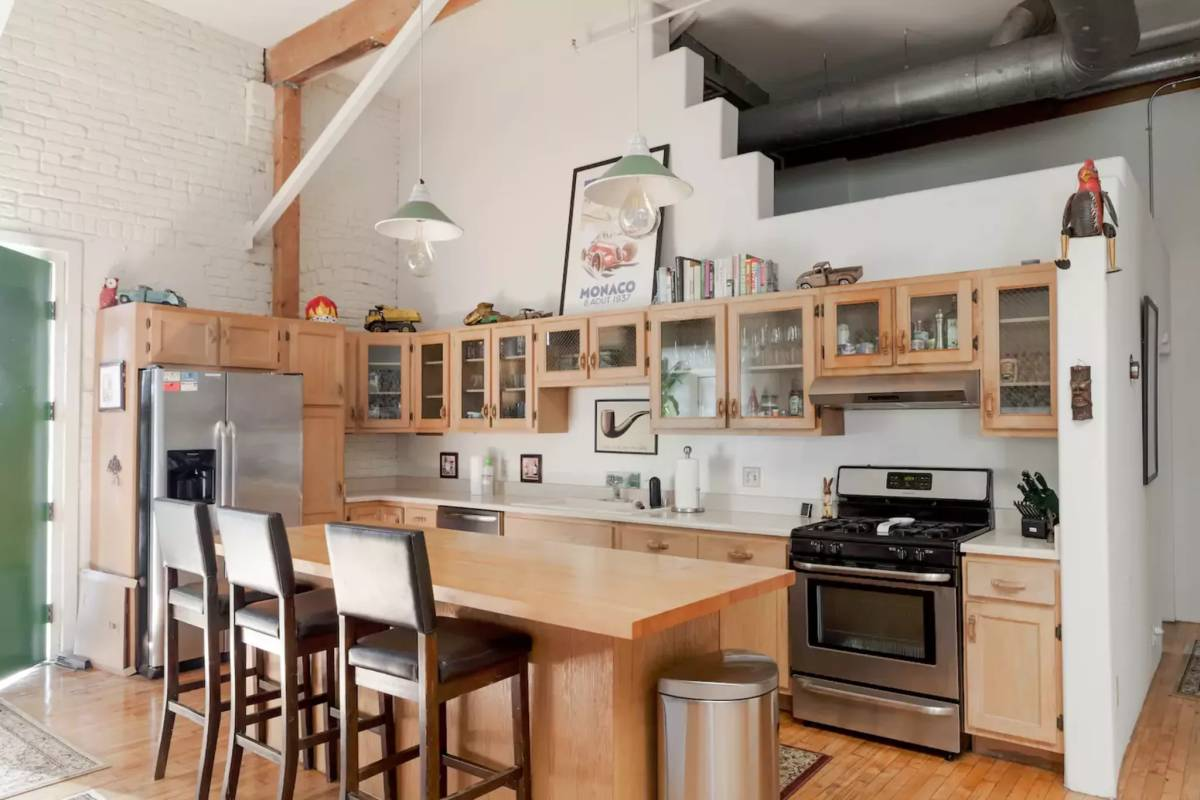 Urban loft kitchen design with wooden furniture and builtin freezer.